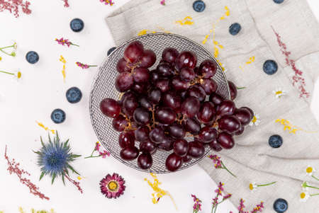 Red grapes on a bowl from above with blueberries and some wild flowers