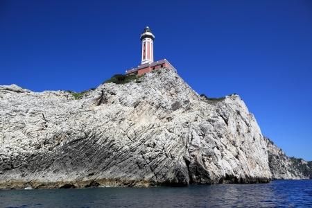 Rocky shore with a lighthouse, Capri island (Italy) Stock Photo