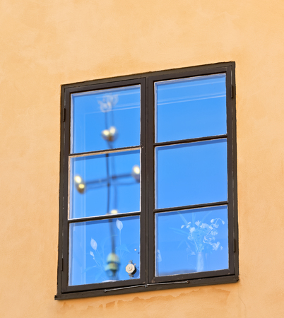 Window with reflection of blue sky and a cross on the yellow wall, Stockholm (Sweden). Image assembled from two frames photo