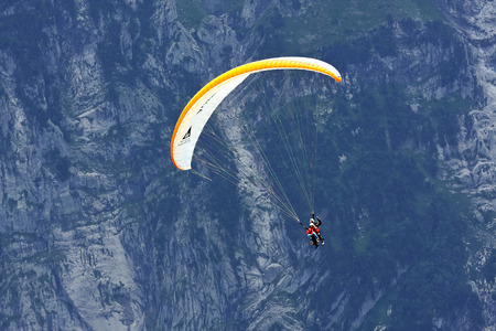 interlaken: Tourist and instructor make paragliding on the background of vertical rock wall (height of about 1000 meters) in the Swiss Alps, Grindelwald (Switzerland)