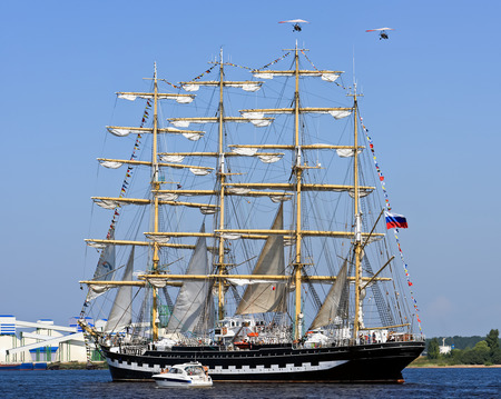 barque: RIGA, LATVIA - JULY 28, 2013: The four-masted barque Kruzenshtern (or Krusenstern) runs along the river Daugava to be released in the Gulf of Riga Baltic Sea during the final parade of regatta sailing yacht The Tall Ships Races 2013. Image assembled fro
