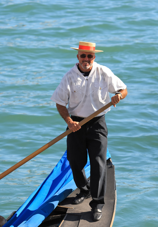 believed: VENICE, ITALY - SEPTEMBER 08, 2012  Portrait of a Venetian gondolier in traditional dress - black shoes and pants, a striped shirt and a straw hat with a ribbon  It is believed that the gondolier - it does not work and is not a profession, a vocation and