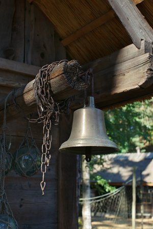 Old ship bell in the fishing village, Latvia Stock Photo