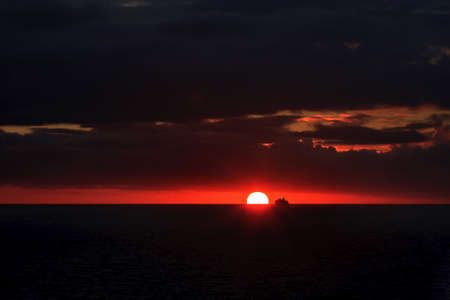 Silhouette of a ship at sunset in the ocean Stock Photo
