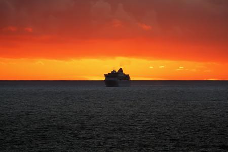 Passenger ship at sunset in the ocean Stock Photo