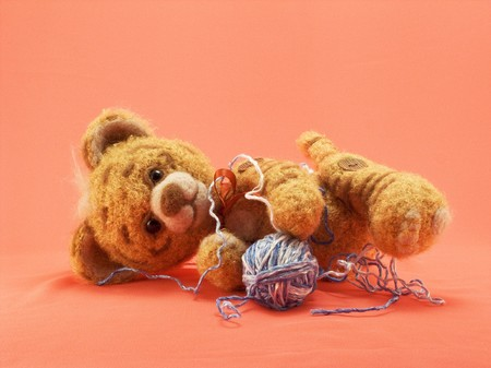 The toy knitted tiger from a wool plays with a ball of threads Stock Photo - 6964766
