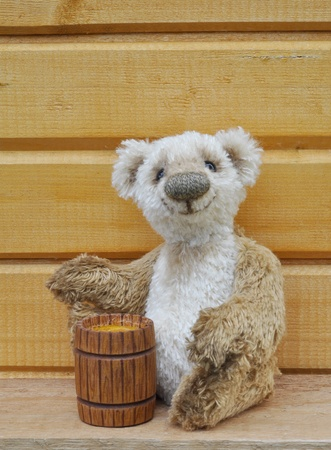 Handmade, the sewed toy: Teddy bear George with a honey keg before a wooden wall photo