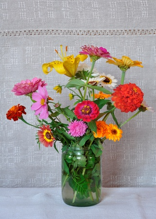 A bouquet of garden flowers in a glass jar on the background of an old linen canvas. August, the Central Russia Stock fotó