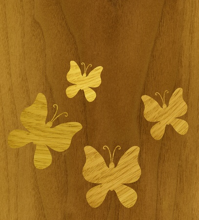 Marquetry, butterflies of ash wood veneer against the background of teak wood photo