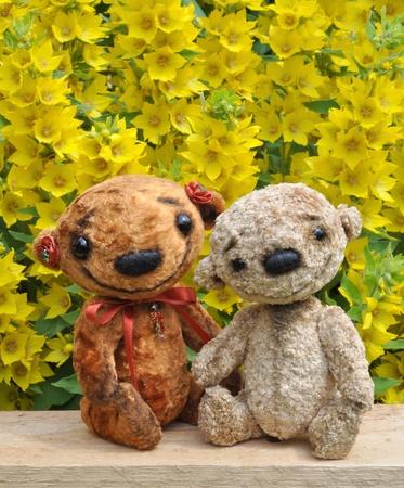 Teddy draagt op een bord tussen de bloemen Handgemaakt, de genaaid pluchen speelgoed
