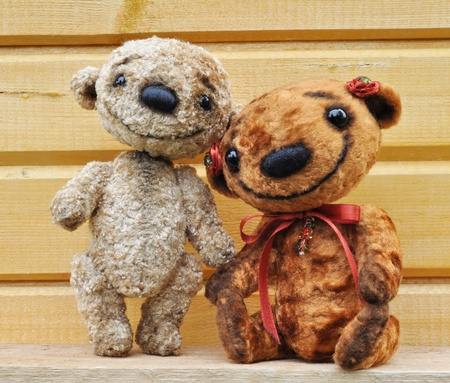 Teddy bears against a wooden wall  Handmade, the sewed plush toys photo