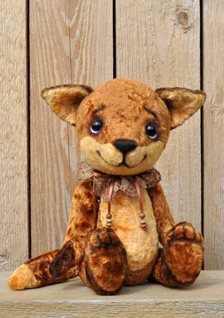Ron fox cub on the background of a wooden plank wall  Handmade, the sewed plush toy photo