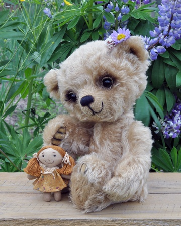 Teddy-bear Lucky with a rag doll on the board against a background of flowers  Handmade, the sewed toy photo
