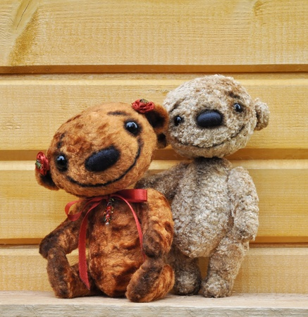 Teddy bears against a wooden wall  Handmade, the sewed plush toys 版權商用圖片