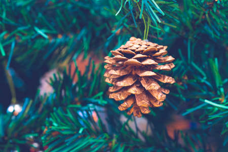 Pine cone on a christmas tree. Christmas concept. Artifical pine branches in the background.
