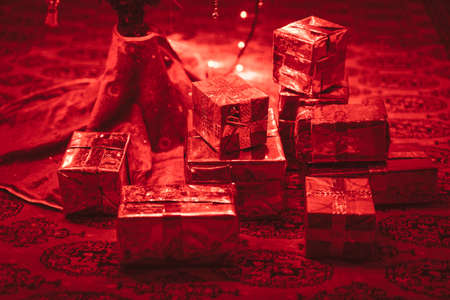 Handmade christmas present under christmas tree. Red christmas lights illuminates the gift box.