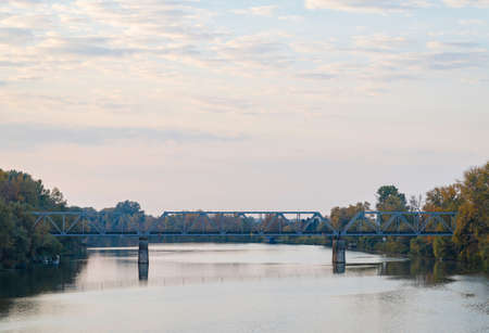 Beautiful river at sunset. Railway bridge over the river in the distance. Trees on the riverbank. Banco de Imagens