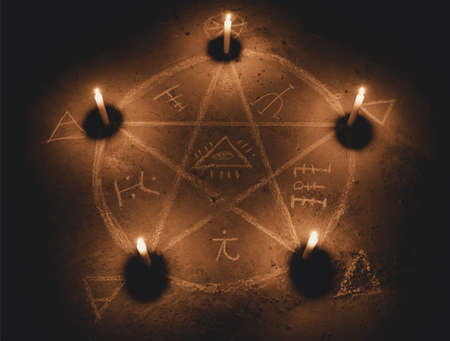 White pentagram symbol on concrete ground. Illuminated with candles. Dark background. Scary, mystical occultism