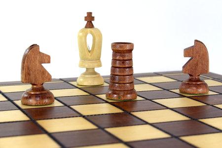チェスボードでは、2頭の黒い馬とルークのボートが白い王に小切手とマットを発表しました 写真素材
