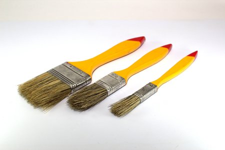 Three paint brushes with a width of 1 inch, 2 inches and 0.5 inches with yellow handles on a white background close-up Reklamní fotografie