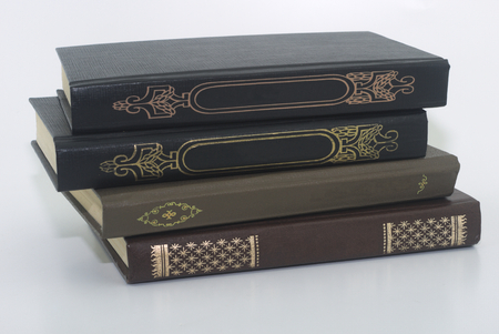 four very old books on a white background close-up