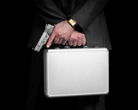 Businessman with gun and silver metal briefcase  Isolated on black