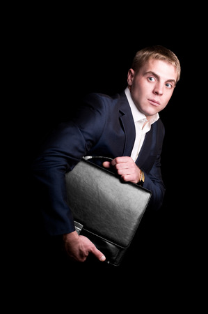 Funny businessman stolen portfolio with money  Isolated on black photo