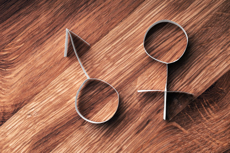 Male and female gender symbols, mars and venus on wooden