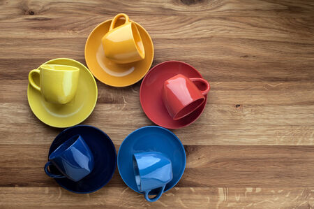 Colorful empty coffee cups on wooden background  photo