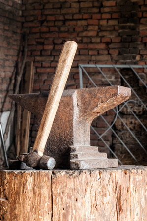 medieval blacksmith: Rustic anvil and hammer on wooden stump.