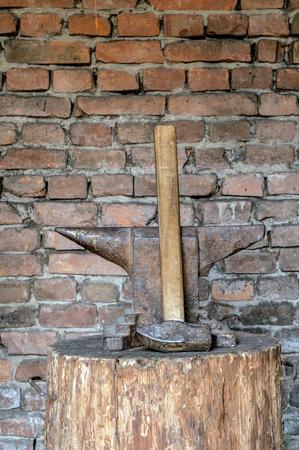 Сельский наковальня и молот на деревянный пень.