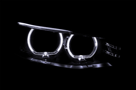 xenon: LED headlights of car on black background. Exterior detail. Stock Photo