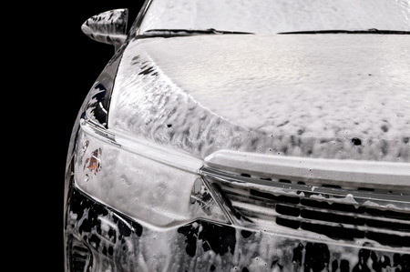 dirty car: Car wash with soap. Modern auto covered by foam.