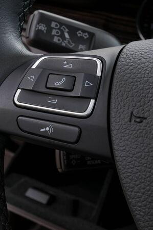handsfree phones: Modern car interior detail. Buttons on steering wheel.