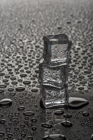 Wet ice cubes on black glossy background.