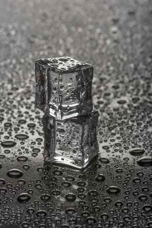 Two wet ice cubes on black glossy background. Vertical studio photo.