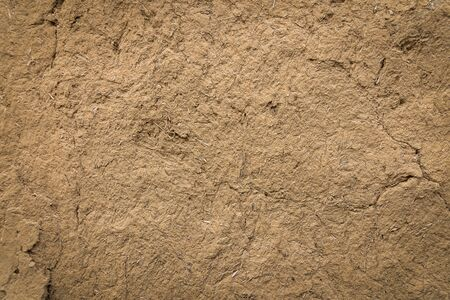 Old clay wall with cracks background.