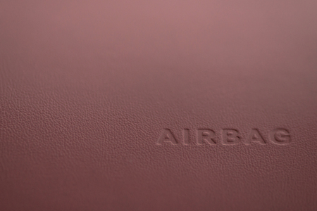 Word Airbag sign on car plastic dashboard. Interior detail.