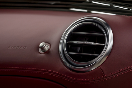 Luxury car leather dashboard. Air conditioning system and airbag panel. Interior detail. Stock Photo