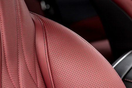 Car interior background. Detail of modern business car perforated leather seat with stitch.