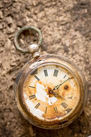 Old silver broken pocket watch on wooden background.