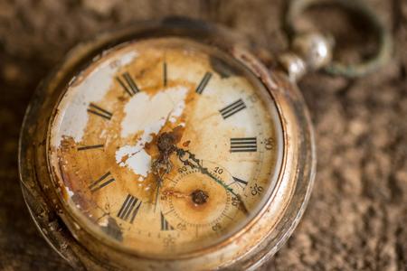 Antique silver broken pocket watch on wooden background. Stock Photo