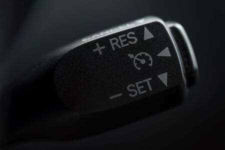 Speed limitation control buttons on modern car. Interior detail. Macro.