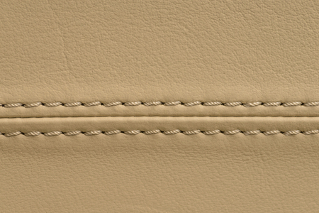 Car leather seat background with stich. Interior detail. Macro photo.