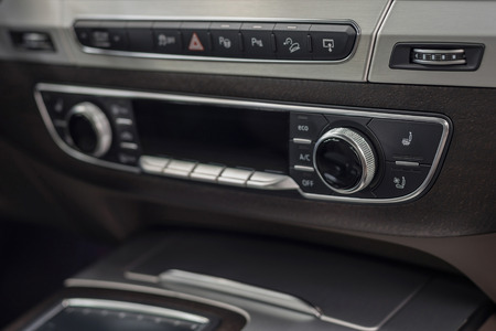 Modern car dashboard with control buttons. Interior detail.