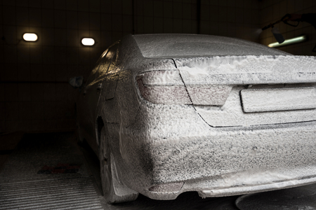 Car wash with soap. Modern car covered by foam. Horizontal photo.