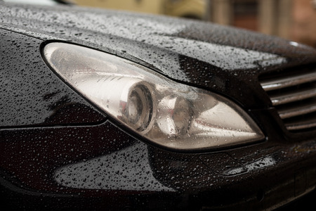 Modern car headlights with water drops. Transportation background.