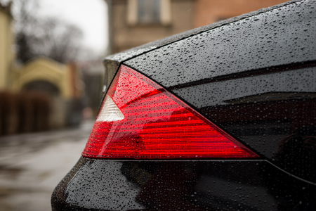 Tail light car with water drops. Exterior detail.