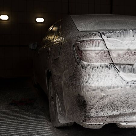 Car wash with soap. Modern car covered by foam.