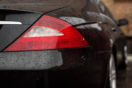 Tail light car with water drops. Exterior detail background.